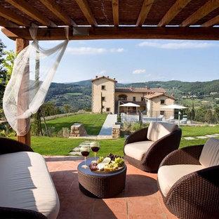 Ispirazione per un patio o portico mediterraneo di medie dimensioni con piastrelle e una pergola