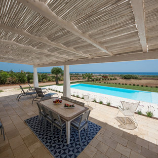 This is an example of a mediterranean back patio in Bari with natural stone paving and an awning.