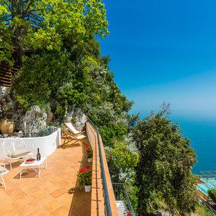 Idee per un patio o portico mediterraneo dietro casa con piastrelle e nessuna copertura