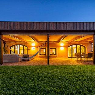 Immagine di un patio o portico mediterraneo con un tetto a sbalzo e pavimentazioni in mattoni