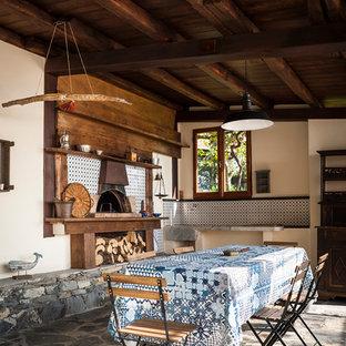 Ispirazione per un patio o portico mediterraneo con pavimentazioni in pietra naturale e un caminetto
