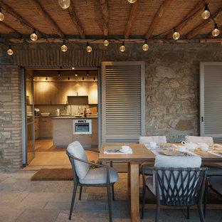 Immagine di un patio o portico mediterraneo dietro casa con pavimentazioni in pietra naturale e una pergola