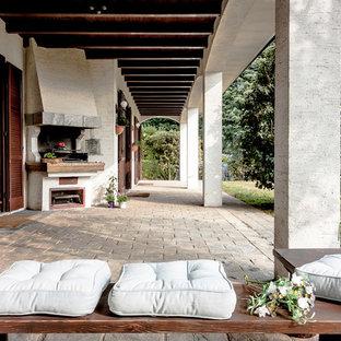 Esempio di un grande patio o portico country dietro casa con pavimentazioni in pietra naturale e un tetto a sbalzo