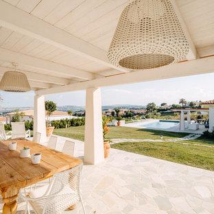 Immagine di un patio o portico mediterraneo dietro casa con piastrelle e un tetto a sbalzo