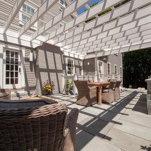 Esempio di un grande patio o portico minimalista nel cortile laterale con pavimentazioni in pietra naturale e una pergola