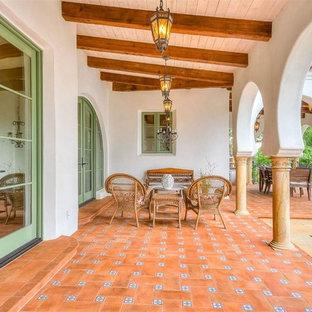 Immagine di un grande patio o portico mediterraneo dietro casa con piastrelle e un tetto a sbalzo