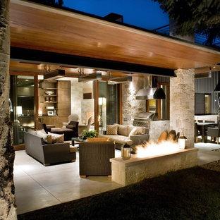 Aménagement d'une terrasse contemporaine avec un foyer extérieur et une extension de toiture.