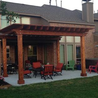 Patio - large traditional backyard concrete patio idea in Houston with a pergola