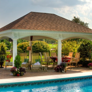 Example of a large transitional backyard stone patio kitchen design in Boston with a gazebo