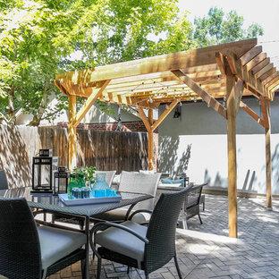 Exemple d'une terrasse arrière romantique de taille moyenne avec des pavés en brique et un gazebo ou pavillon.