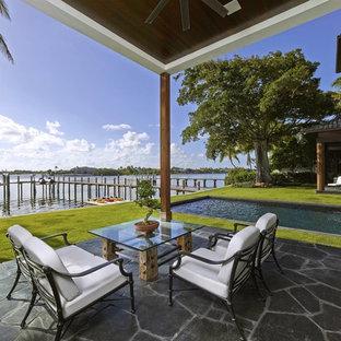 Immagine di un ampio patio o portico etnico dietro casa con pavimentazioni in pietra naturale e un tetto a sbalzo