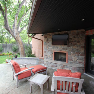 Mid-sized elegant backyard brick patio photo in Other with a fire pit and a roof extension