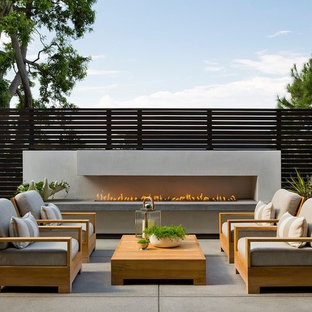 Photo of a contemporary patio in Los Angeles with concrete slabs, no cover and a fireplace.