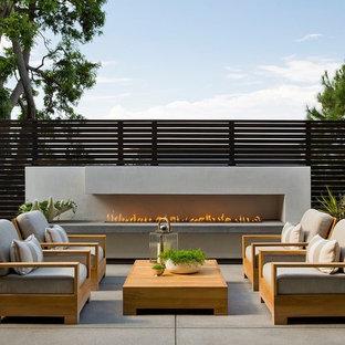 Cette image montre une terrasse design avec une dalle de béton, aucune couverture et une cheminée.