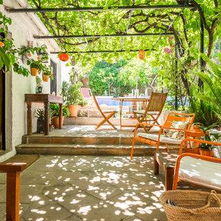 Foto di un grande patio o portico country dietro casa con piastrelle e una pergola