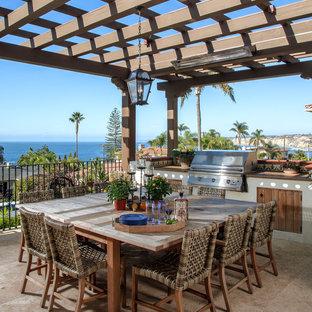 Idée de décoration pour une terrasse avec une cuisine extérieure latérale méditerranéenne de taille moyenne avec une pergola et du carrelage.