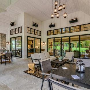 Immagine di un grande patio o portico country dietro casa con un tetto a sbalzo e pavimentazioni in pietra naturale