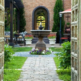 This is an example of a medium sized mediterranean back patio in Denver with an outdoor kitchen, brick paving and a pergola.