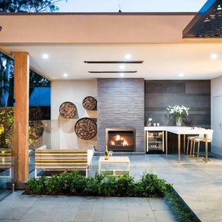 Design ideas for a contemporary backyard patio in Melbourne with natural stone pavers, a roof extension and with fireplace.