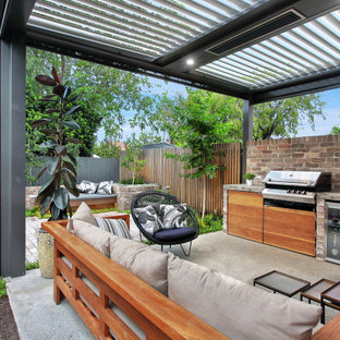 Mid-sized contemporary backyard patio in Sydney with an outdoor kitchen, brick pavers and a roof extension.