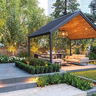 Ispirazione per un patio o portico contemporaneo con lastre di cemento e un gazebo o capanno