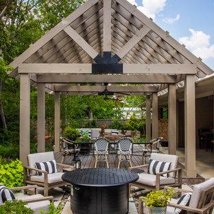 Cette image montre une terrasse arrière traditionnelle avec des pavés en béton.