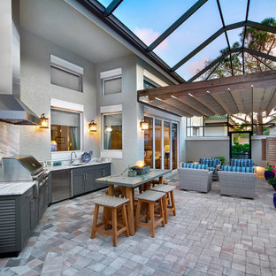 Example of a large transitional backyard stone patio kitchen design in Other with a roof extension