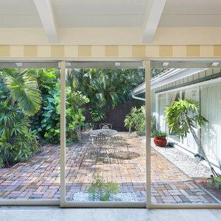 Ispirazione per un patio o portico tropicale di medie dimensioni e dietro casa con pedane e un tetto a sbalzo