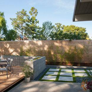 Esempio di un patio o portico moderno di medie dimensioni e dietro casa con cemento stampato e un tetto a sbalzo