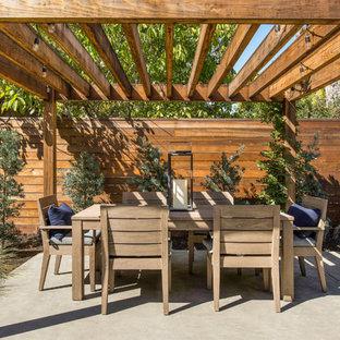 Aménagement d'une terrasse arrière campagne avec une dalle de béton et une pergola.