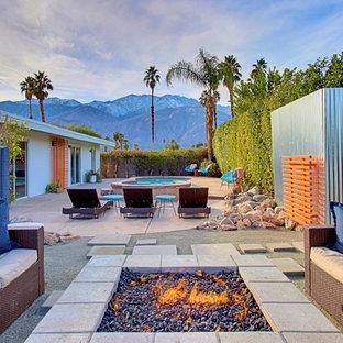 Immagine di un grande patio o portico minimalista davanti casa con un focolare, graniglia di granito e nessuna copertura