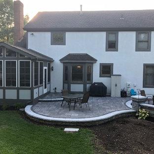 Idee per un ampio patio o portico eclettico dietro casa con un focolare e pavimentazioni in mattoni