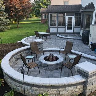 Ispirazione per un ampio patio o portico eclettico dietro casa con un focolare e pavimentazioni in mattoni