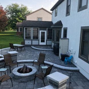 Idee per un ampio patio o portico boho chic dietro casa con un focolare e pavimentazioni in mattoni