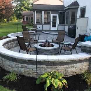 Foto di un ampio patio o portico eclettico dietro casa con un focolare e pavimentazioni in mattoni