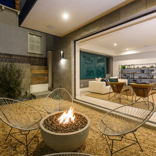 Trendy front yard gravel patio photo in Los Angeles with a fire pit and a roof extension