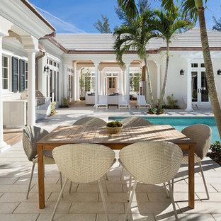 Esempio di un patio o portico tropicale di medie dimensioni e dietro casa con cemento stampato e un tetto a sbalzo