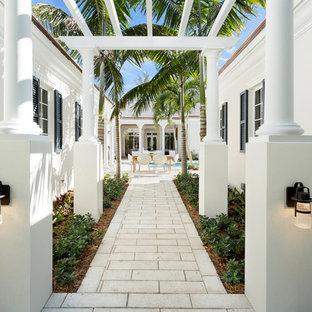 Immagine di un grande patio o portico tropicale nel cortile laterale con pavimentazioni in pietra naturale