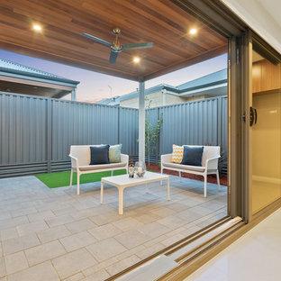 Immagine di un piccolo patio o portico moderno dietro casa con pavimentazioni in mattoni e un tetto a sbalzo