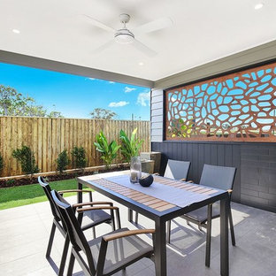Photo of a contemporary backyard patio in Brisbane with concrete pavers and a roof extension.