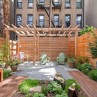 Small trendy backyard stone patio photo in New York with a pergola