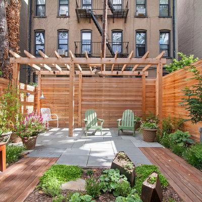 Small trendy backyard stone patio photo in New York with a pergola