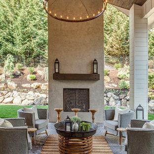 Exemple d'une terrasse arrière nature avec du béton estampé, une extension de toiture et une cheminée.