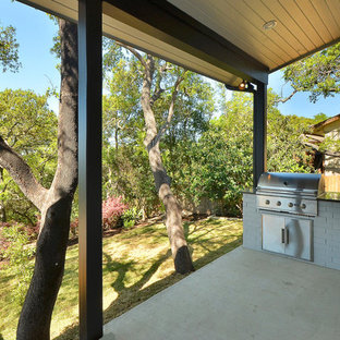 Inspiration for a modern backyard concrete patio kitchen remodel in Austin with a roof extension