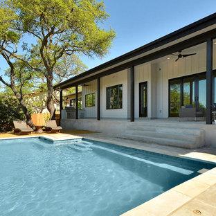 Idee per un patio o portico minimalista dietro casa con lastre di cemento e un tetto a sbalzo