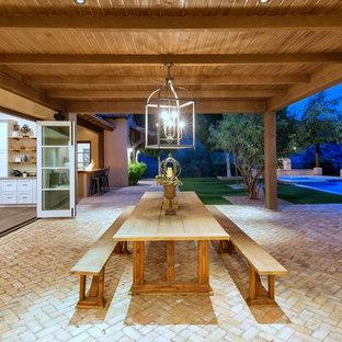 Patio kitchen - mediterranean backyard brick patio kitchen idea in Phoenix with an awning