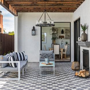 Idee per un patio o portico mediterraneo dietro casa con un caminetto, piastrelle e una pergola
