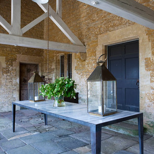 This is an example of a large rural back patio in Gloucestershire with natural stone paving and a roof extension.