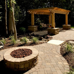 """A Dry Creek Bed Runs Through It - The fire pit and cedar pergola make this a comfortable yard both day and night.  A narrow stream/dry creek bed separates the fire pit patio from the pergola-patio. The small bridge over the """"creek"""" is natural stone. Note the bases of the pergola posts are wrapped with the same modular block used in the fire pit. (That's lava rock in the fire pit."""