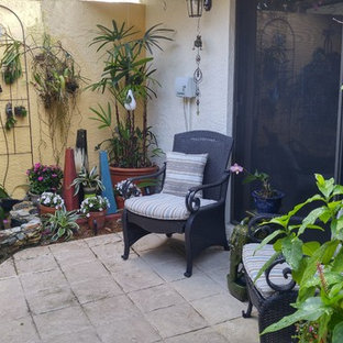 Small eclectic courtyard patio in Miami with a living wall, an awning and stamped concrete.